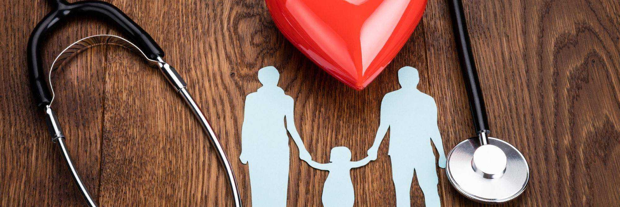 High Angle View Of Red Heart And A Stethoscope With Family Papercut On Wooden Desk